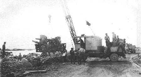 Lowering a 3-inch anti-aircraft gun into position